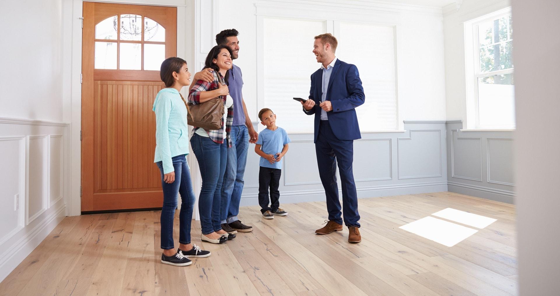 Immobilienmakler führ Familie durch ihr neues Zuhause